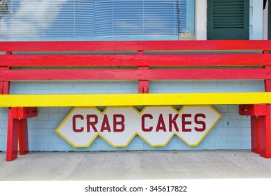Crab Cakes Sign on Blue Wall Under Bright Red and Yellow Bench
