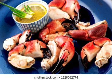 Crab claws in blue plate with lemon and oregano.