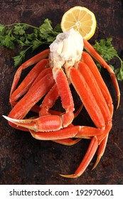 Crab legs with lemon and parsley on brown background