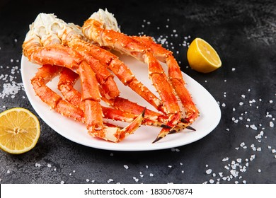 Crab legs in a plate on a dark background. Ready to eat.