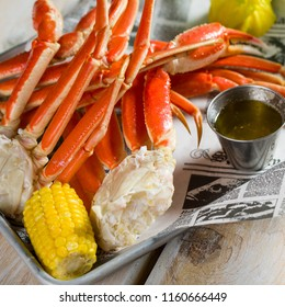 Crab legs and yellow corn n a silver tray
