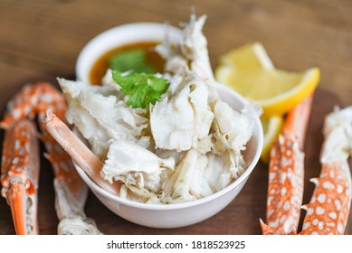 Crab meat / Cooked crab claws and legs on white bowl and seafood sauce on the table , blue swimming crab