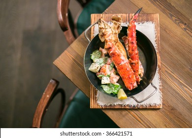 Crab phalanges with salad aside in a metal pan on a wooden table from above