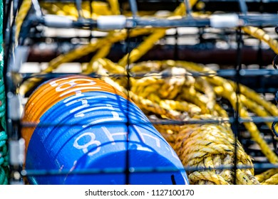 Crab pot fishing gear with yellow coiled polypropylene rope and buoys waiting to be launched into the ocean to catch seafood.