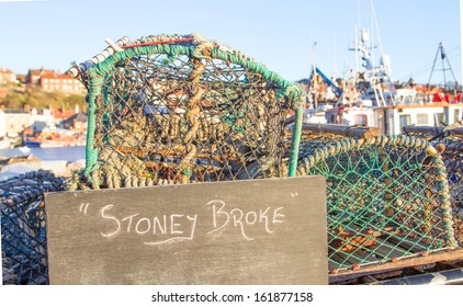 "crab pots and blackboard with ""stoney broke"" in front of harbour - poor fishermen concept"