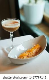 Crab salad with orange in white bowl