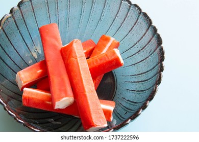 Crab sticks in plate on blue background closeup