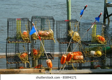 Crab traps stored on a dock in Little River, South Carolina. Colorful floats stored inside the wire frames make a bright contrast with the blue water background.