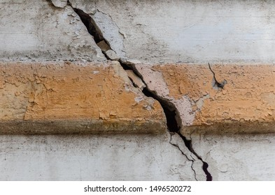 A crack in the concrete wall of the house with a yellow strip in the middle close-up