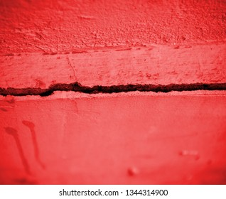 Crack in the red concrete wall. Abstract background for design