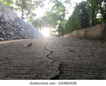 Crack of the road with Sunshine.Cracks, crevices, concrete slabs this is caused by the non-standard construction in Park.