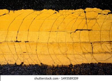 Crack yellow line painted on asphalt road