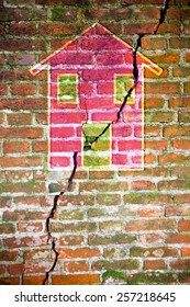 Cracked brick wall with a colored house drawn on it