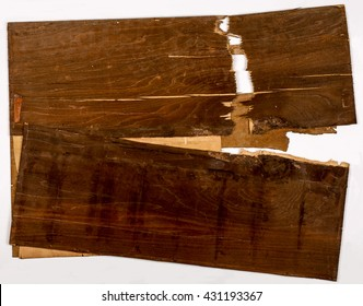 Cracked broken layers on old plywood with dark brown paint white background