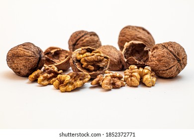 cracked and closed walnuts and their shells in front of a white background