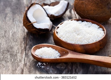 Cracked  coconut and flakes on rustic wooden table background