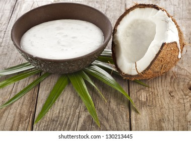 cracked coconut with milk cream in a clay bowl on wooden table surface
