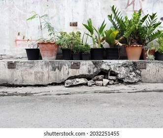 Cracked concrete old wall longs deep, large hole outside under house. Part of the foundation wall moves collapsed and grounds floor hollows. Concept life unsafe, dangerous, damaged building structure.