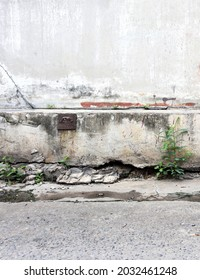 Cracked concrete old wall longs deep, large hole outside under house. Part of foundation wall moves collapsed and ground hollows. Concept life unsafe dangerous, damaged building structure copy space