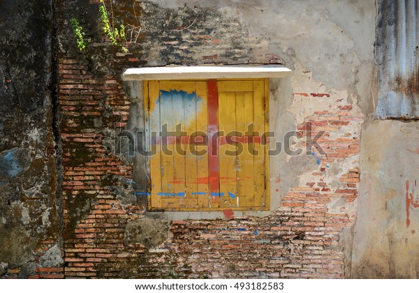 Cracked concrete on old brick wall with window texture background for wallpaper