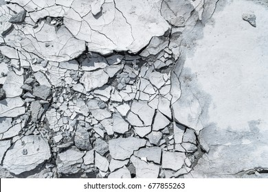 Cracked concrete texture background. Grey surface with cracks close up. A lot of pieces of splintered plaster. Abstract concept of split, dissent, disagreement, discord. Sunny day with shadows.