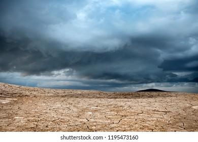 Cracked dry landscape over stormy sky