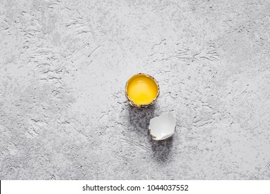 Cracked easter quail egg and eggshell on concrete background. Top view, space for text.