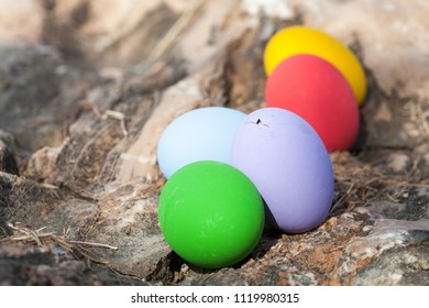 Cracked egg and colorful easter eggs on stone texture background