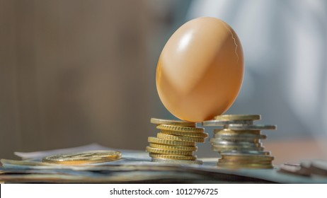 Cracked Egg Put On Top Of Stacked Coins On Pile Of US Dollar Banknote above black leather wallet, Use As Risky / Weakness Of Virtual Money Concept.