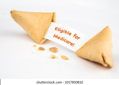 "CRACKED FORTUNE COOKIE WITH WORD ""Eligible for Medicare!"" ON WHITE SLIP PAPER / HEALTH CARE CONCEPT"