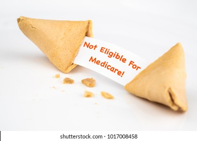 "CRACKED FORTUNE COOKIE WITH WORD ""Not Eligible for Medicare!"" ON WHITE SLIP PAPER / HEALTH CARE CONCEPT"