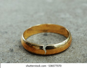 Cracked gold wedding ring -- divorce or infidelity concept                              - Shutterstock ID 538377070