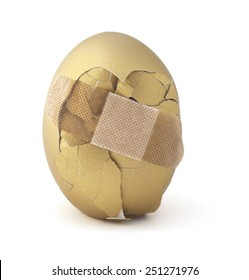Cracked golden egg isolated on a white background.