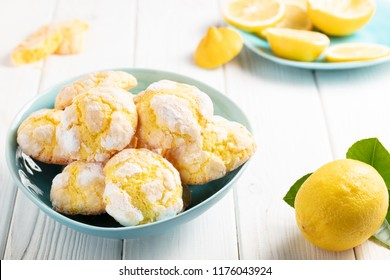 Cracked Lemon cookies in blue plates on white wooden background