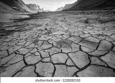 Cracked mudflats with Mount Breadablik and Thor on the horizon in Akshayuk Pass, Nunavut, Baffin Island