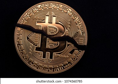 Cracked on two pieces bitcoin coin isolated on black background