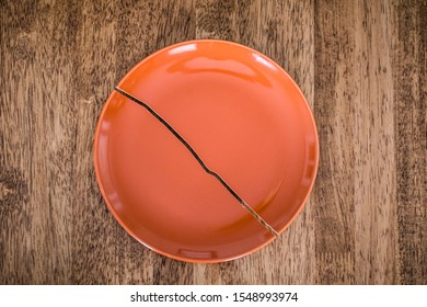 A cracked orange plate sits on a brown wooden table with copy space