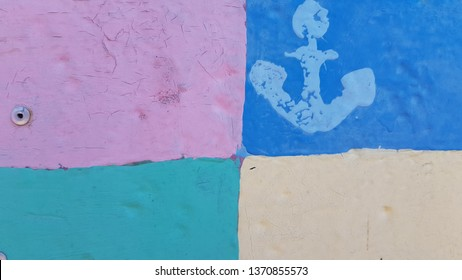 Cracked paint stamped anchor silhouette on uneven surface of squared painted background. Colorful grunge backdrop nautical style. Blue marine symbol stamped on old painted scratched metal gates.
