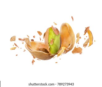 Cracked pistachio frozen in the air on a white background