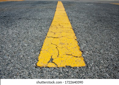 A cracked road with a yellow line in the middle.