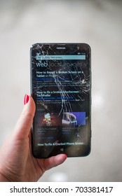 """Cracked screen smartphone in hand. Holding broken smartphone. Smartphone browser search """"How to repair broken screen"""""""