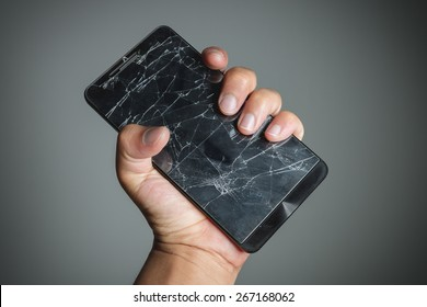 Cracked smartphone in hand holding.