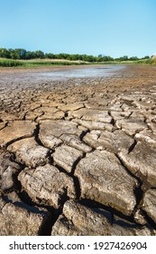 Cracked soil on riverbank of dried waterless river in summer drought.