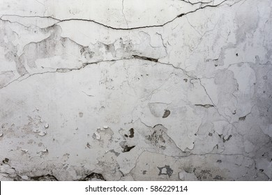 Cracked stone texture plastered white walls. Vintage cracks in white wall surface. Web small cracks on surface of white background. Traces of destruction of  old cement wall