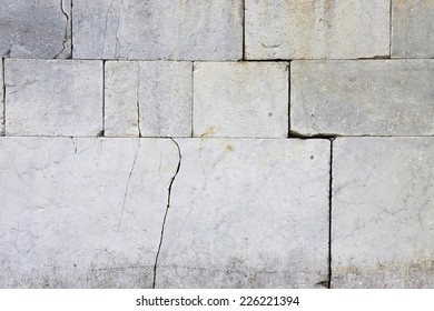 Cracked stone wall - lesion on a stone wall caused by subsidence of the foundation