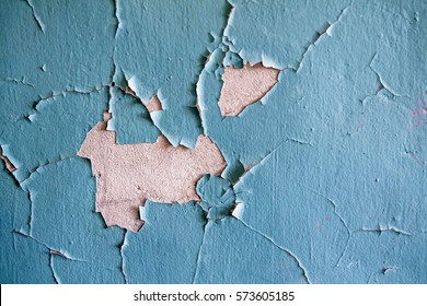 Cracked wall with old layers of paint in abandoned house