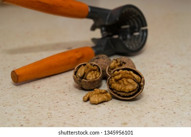 cracked wallnuts with nut cracker in the background