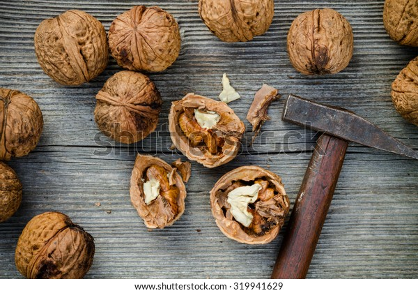 cracked walnuts and hammer on old wooden background - top view