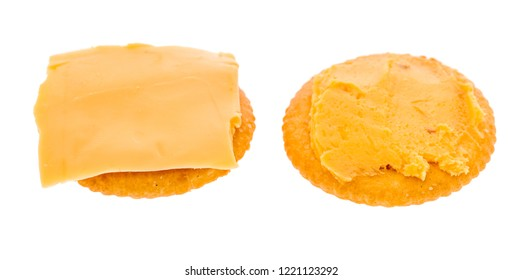 A cracker with cheese spread and another with a  slice of cheese on it on an isolated background