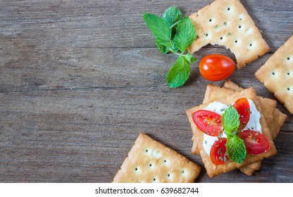 Cracker topped with cream cheese, tomato and mint on wooden background, top view